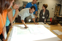 Using a light pen, projector and other equipment, participants at a planning issues workshop in Galveston, Texas, explore different land development scenarios.